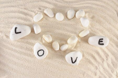 Love word and heart shape on group of stones with sand as background Stock Photo - 13462728