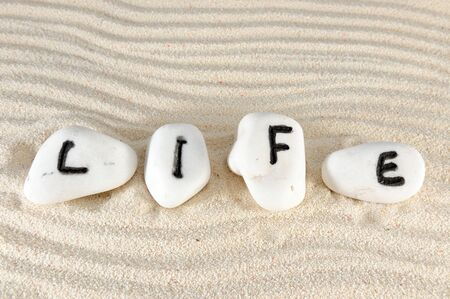 Life word on group of stones with sand as background photo