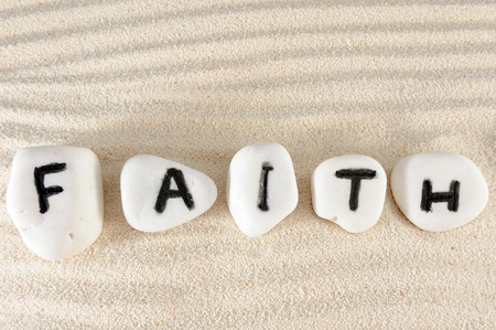 Faith word on group of stones with sand as background photo