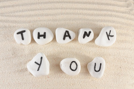Thank you words on group of stones with sand as background