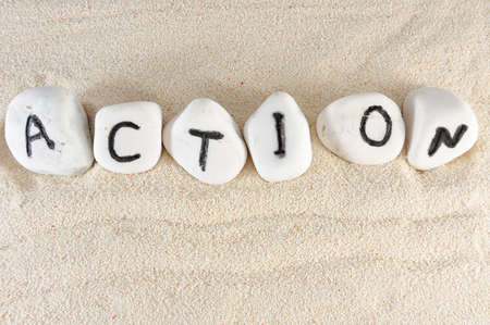 Action word on group of stones on the sand photo