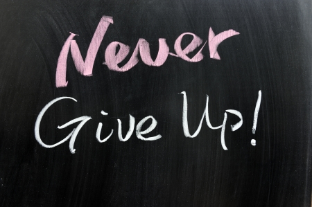 Never give up words written on the chalkboard photo