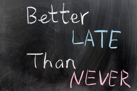 never: Better late than never words written on chalkboard Stock Photo
