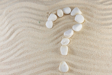 Question mark made of stones with sand as background