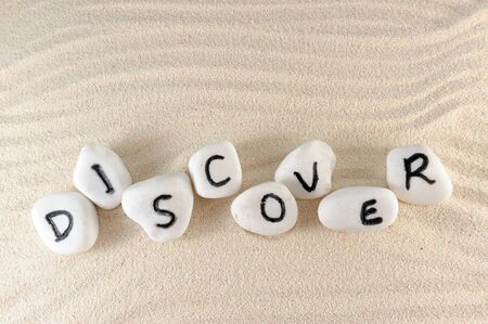discover: Discover word on group of stones with sand as background