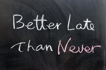 than: Better late than never words written on chalkboard Stock Photo