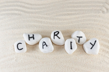 give charity: Charity word on group of stones with sand background
