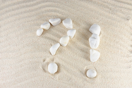 Question and exclamation mark arranged by stones with sand background photo
