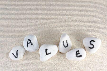 Waarden woord op groep stenen met zand achtergrond