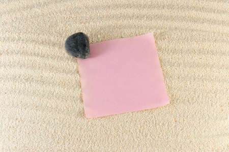 Blank paper on the sand with a stone on it Stock Photo - 13927299