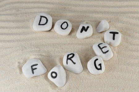 forget: Dont forget words on group of stones with sand background