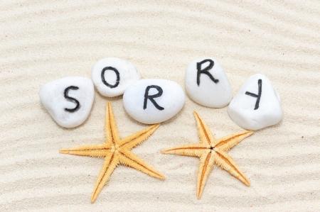 pardon: Désolé mot sur un groupe de pierres avec fond de sable