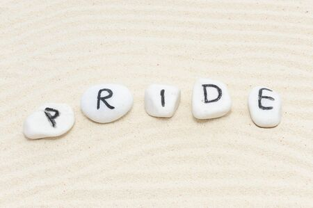 sufficiency: Pride word on group of stones with sand background