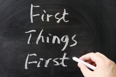 First things first words written on the chalkboard Stock Photo