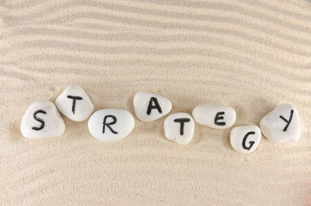 Strategy word on group of stones on the sand Stock Photo - 14167429