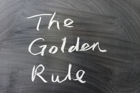by the rules: The golden rule words written on the chalkboard Stock Photo