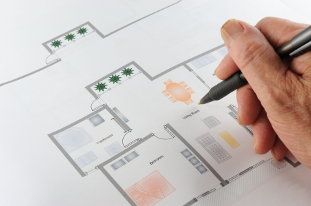 Colorful home floor plan with a hand holding a pen on it, three rooms,one living room photo