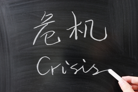 bilingual: Bilingual crisis word in Chinese and English written on the blackboard