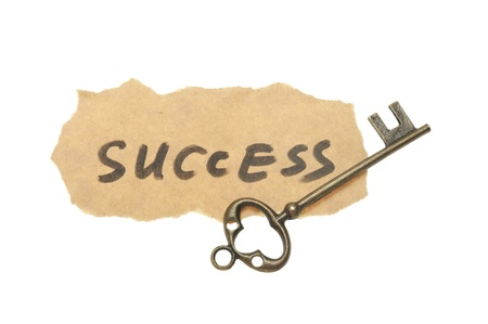 Old key and success words written on old paper photo