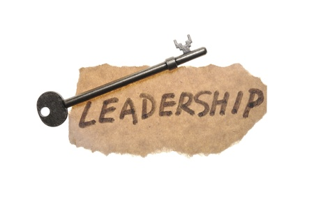key words: Old key and leadership word written on old paper
