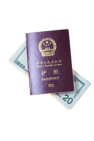 Chinese passport and a pile of US Dollars isolated on white photo