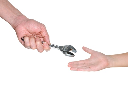 passing over: Two hands handing over wrench isolated on white background Stock Photo