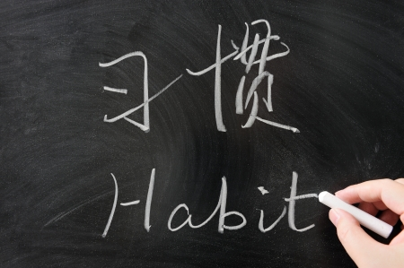 bilingual: Bilingual habit word in Chinese and English written on the blackboard Stock Photo