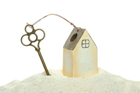 dwell house: key and house model on the sand isolated on white