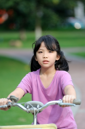 Asian kid riding bike in the park at sunset photo