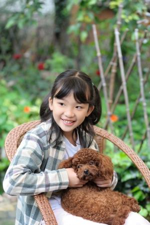 Asian kid sitting and holding poodle dog photo