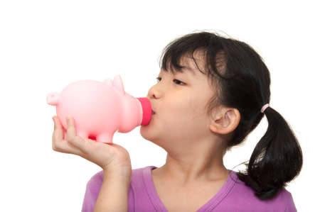 Asian kid kissing piggy bank isolated on white background photo