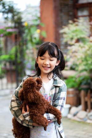 Asian kid standing and holding poodle dog photo