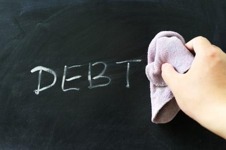Hand wiping off debt word using rug Standard-Bild
