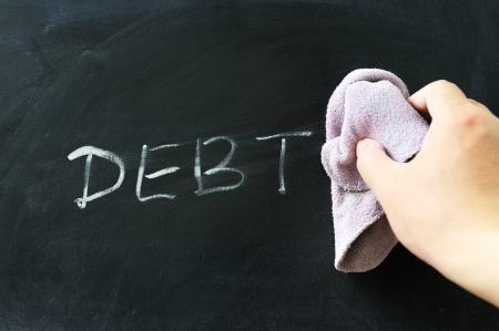 cleaning debt: Hand wiping off debt word using rug Stock Photo