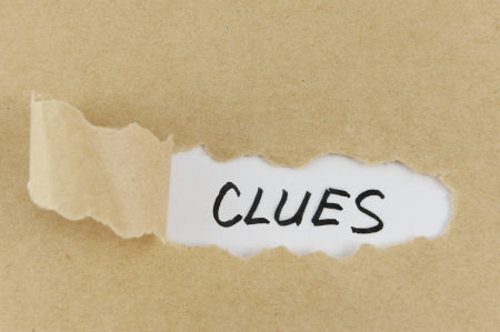 clues: Teared paper with clues word behind it Stock Photo