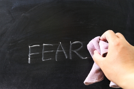 erase: Hand wiping off fear word using rug Stock Photo