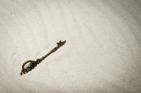 An old style key buried in the sand photo