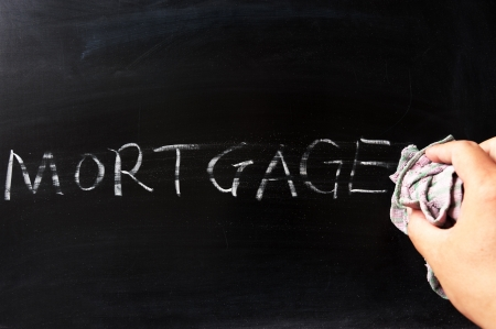 Hand wiping off mortgage on blackboard using rag Stock Photo - 15238818
