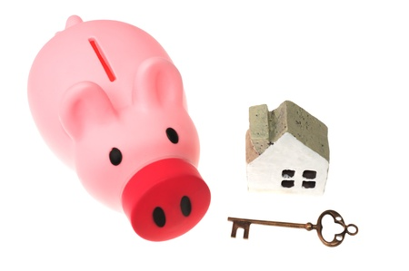 Piggy bank, key and house model isolated on white photo