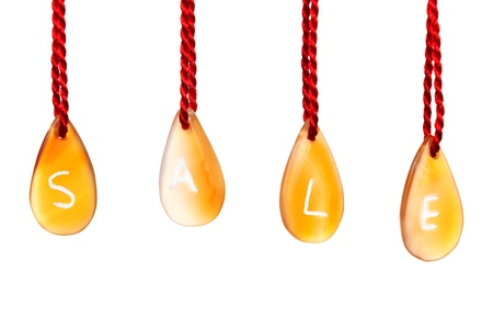 Sale spelled with agates that are engraved with white letters and are hung by ropes, isolated against white background Stock Photo - 15685280