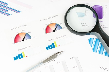 Business graph printed on the white paper with a magnifier on it