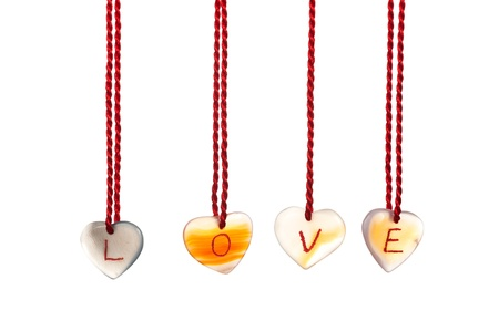 Love word spelled with agates that are engraved with white letters and are hung by ropes, isolated against white background Stock Photo - 15685241