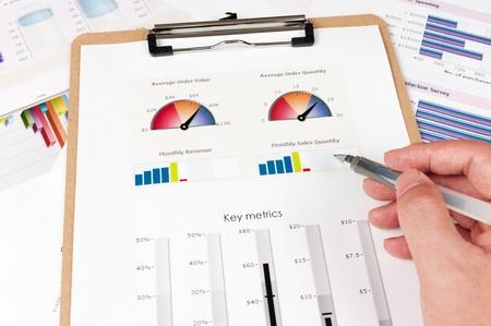 ビジネス グラフ印刷白い紙の上にペンを持つ手 写真素材