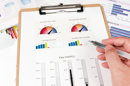metrics: Business graph printed on the white paper with a hand holding a pen on it Stock Photo