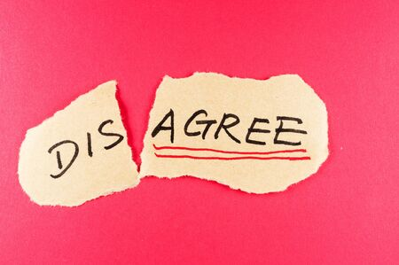 amend: Disagree to agree concept words written on the paper against red background