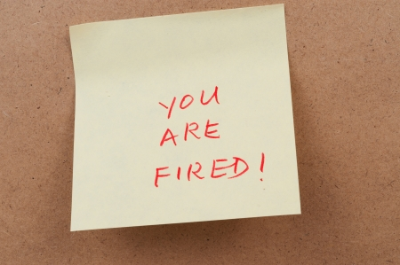 bulletinboard: You are fired words on sticky note attached on the board Stock Photo