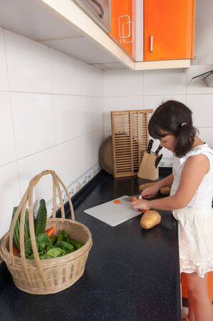Asian kid cutting vegetables in the kitchen photo