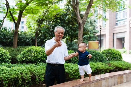 Asian grandfather teaching grandson to walk in the garden