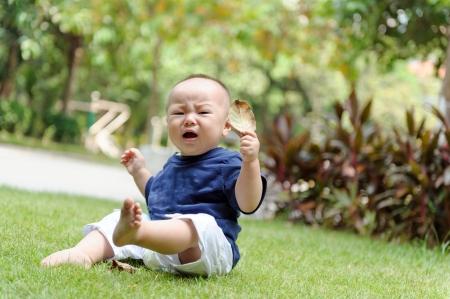 アジアの赤ちゃんが芝生で遊ぶ 写真素材