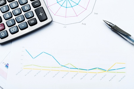 financial service: Business graph printed on white paper with calculator and glasses